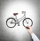 Рука в официально белой рубашке рисует эскиз велосипеда на бетонной стене Стоковые Изображения