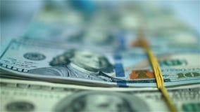 Рука в пачках голубой перчатки moving долларов США на белой поверхности closeup акции видеоматериалы