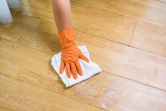 Рука в перчатках очищая деревянный пол с ветошью и cleanser на стоковая фотография