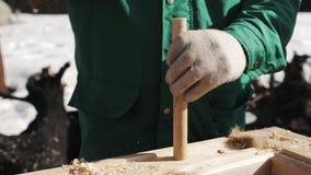 Рука в перчатках работника бить молотком деревянную штангу молотком для того чтобы продырявить в деревянном блоке, внешней зиме акции видеоматериалы