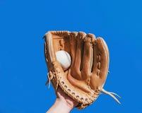 Рука в перчатке для бейсбольного матча уловила кожаный белый шарик дальше стоковое изображение rf