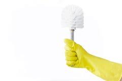 Рука в резиновой желтой щетке владениями перчатки для туалета на белой предпосылке чистка Стоковое Изображение RF
