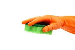 Рука в резиновой перчатке держа отечественную губку Стоковое Изображение