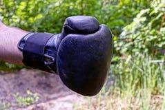 Рука в черной перчатке бокса на улице стоковая фотография