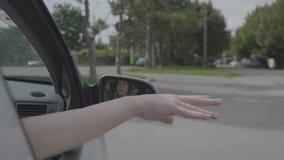 Рука девочка-подростка развевая ее рука вне автомобиля окна во время отключения лета - видеоматериал