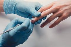 Рука девушки делая маникюр для клиента Стоковые Фотографии RF