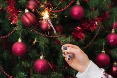 Рука девушки держа горя взрыв и рождественскую елку бенгальского огня стоковое изображение
