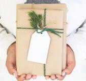 Рука девушки держа ремесло и handmade подарочные коробки подарка на рождество с биркой Стоковое Изображение