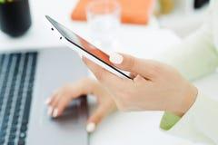 Рука девушки держа умный телефон Стильное современное рабочее место офиса на предпосылке Стоковые Фото