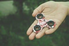 Рука девушки держит и показывает игрушку обтекателя втулки непоседы руки стоковое фото