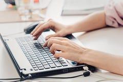 рука девушки печатая на портативном компьютере на деревянном столе Стоковые Фото