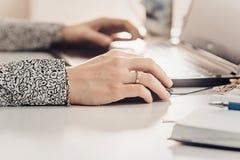рука девушки печатая на портативном компьютере на деревянном столе Стоковые Изображения