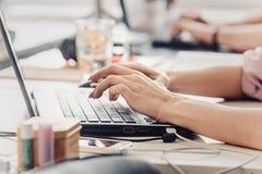 рука девушки печатая на портативном компьютере на деревянном столе стоковое фото