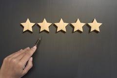 Рука дела выбирает оценку 5 звезд на деревянном Стоковые Изображения