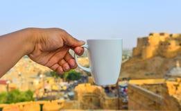 Рука держа белую чашку стоковое изображение rf