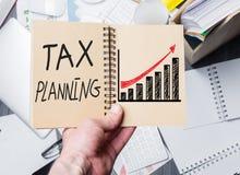 Рука держа блокнот планирования налогов стоковые фотографии rf