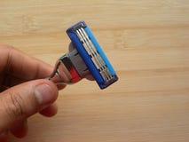Рука держа брить бритву стоковое фото