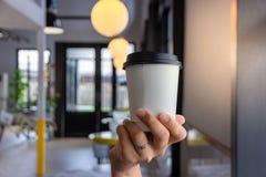 рука держа бумажный стаканчик кофе стоковое изображение rf