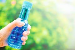 Рука держа бутылку питьевой воды Стоковые Фотографии RF