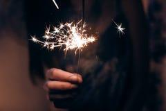 Рука держа горящий свет Бенгалии фейерверка Космос для текста Бушель Стоковое фото RF