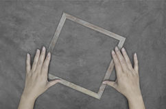 Рука держа деревянную рамку на бетонной стене Стоковая Фотография RF