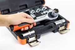Рука держа инструмент Инструментальный ящик для автомобиля Изолированный на whi стоковые фото