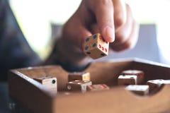 Рука держа и играя деревянная dices Стоковое Фото