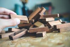 Рука держа и играя игра блока башню Jenga или падения деревянная стоковые фотографии rf