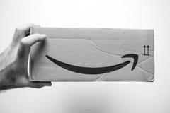 Рука держа картонную коробку с логотипом улыбки логотипа Амазонки Стоковые Фото