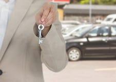 Рука держа ключевой перед автомобилями Стоковая Фотография