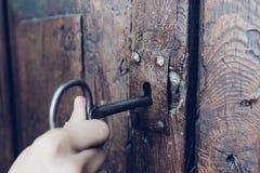 Рука держа ключ металла винтажный к открывать старое секретное деревянное делает стоковая фотография rf