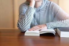 Рука держа книгу дома стоковое изображение