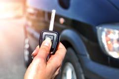 Рука держа кнопку на удаленном автомобиле В селективном фокусе женщины рука отжимает на аварийных системах автомобиля дистанционн Стоковая Фотография