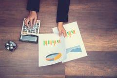Рука держа лист диаграммы и отжимая калькулятор стоковые изображения