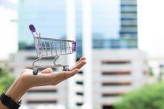 Рука держа магазинную тележкау Отображайте польза для магазина торгового центра, онлайн и автономных, выходя розничную концепцию  стоковые фото