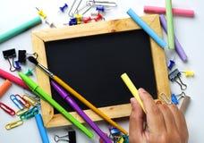 Рука держа мелок Пустое классн классный деревянной рамки между школой стоковые изображения