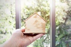 Рука держа модельный деревянный дом на предпосылке Думать и мечта стоковые изображения rf