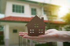 Рука держа модельный дом, свойство ссуды под недвижимость для концепции стоковые изображения