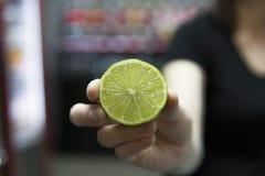 Рука держа половину зеленой известки Половины известки в руке над баром на предпосылке Творческое и стильное instagram Стоковое фото RF