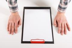 Рука держа пустую доску зажима с модель-макетом дизайна белой бумаги Стоковые Фотографии RF