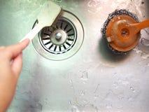 Рука держа раковину нержавеющей стали чистки щетки Стоковые Фото
