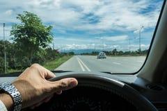 Рука держа рулевое колесо около дороги для безопасного привода Стоковая Фотография