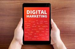 Рука 2 держа таблетку с маркетингом цифров и словом характеристики стоковая фотография