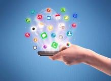 Рука держа телефон таблетки с значками app стоковая фотография