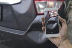 Рука держа умный телефон принимает фото на сцену cras автомобиля стоковые изображения rf