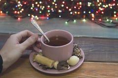 Рука держа чашку чаю с чайной ложкой и поддонником, fairy светами Стоковое Изображение