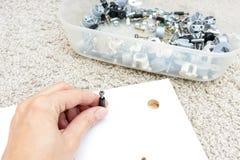 Рука держа штуцер, отладку или крепежную деталь для мебели установки собирая сделанной макулатурного картона стоковые изображения rf