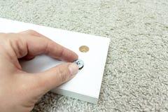Рука держа штуцер, отладку или крепежную деталь для мебели установки собирая сделанной макулатурного картона стоковое изображение rf