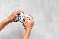 Рука держа gamepad на серой конкретной предпосылке Человек при регулятор играя видеоигру дома Отдых и зрелищность видео стоковые изображения rf