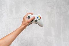 Рука держа gamepad на серой конкретной предпосылке Человек при регулятор играя видеоигру дома Отдых и зрелищность видео стоковые фото